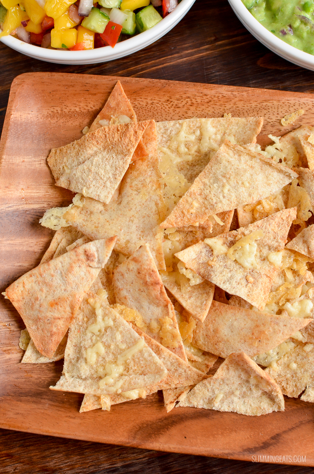 close up of cheddar pita chips on wooden plate
