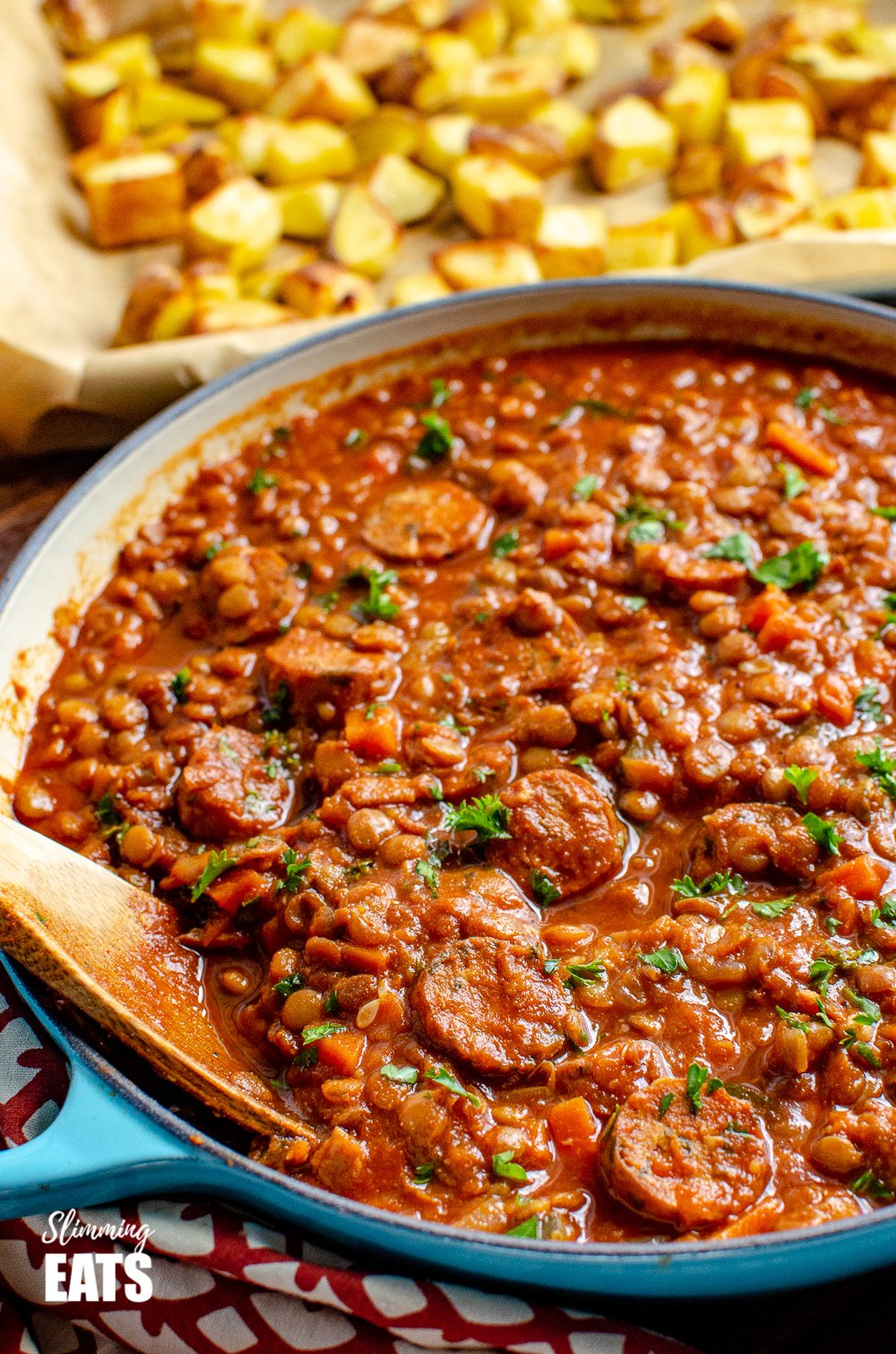 One Pot Sausage and Lentil Casserole in le creuset cast iron pan with wooden spoon