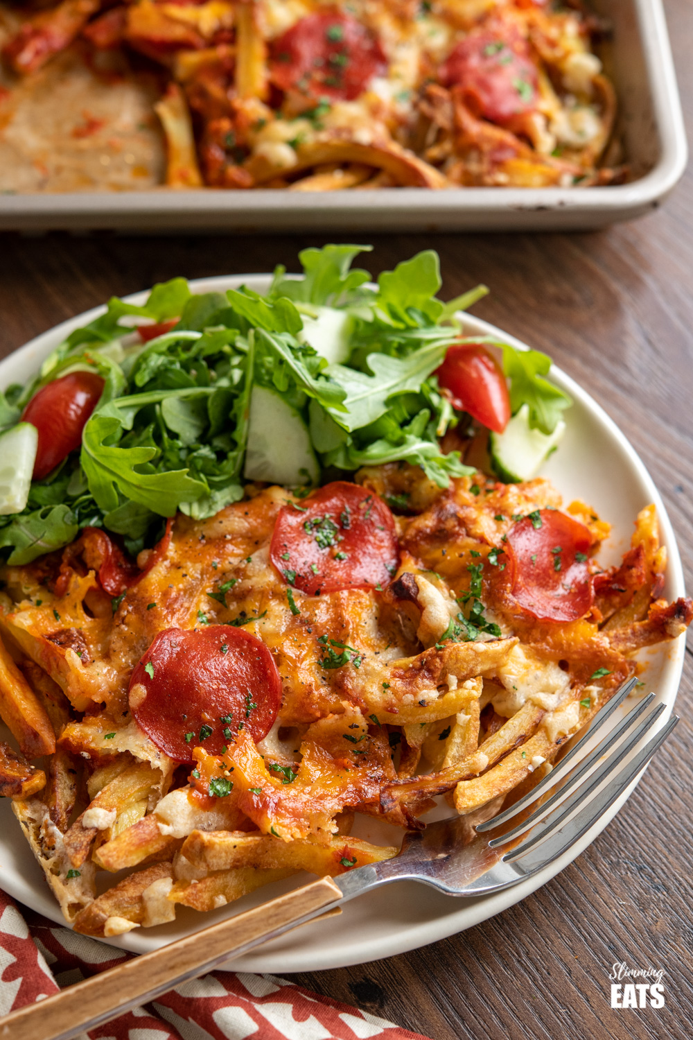 Cheesy Oven Baked Pizza Fries on cream plate with salad