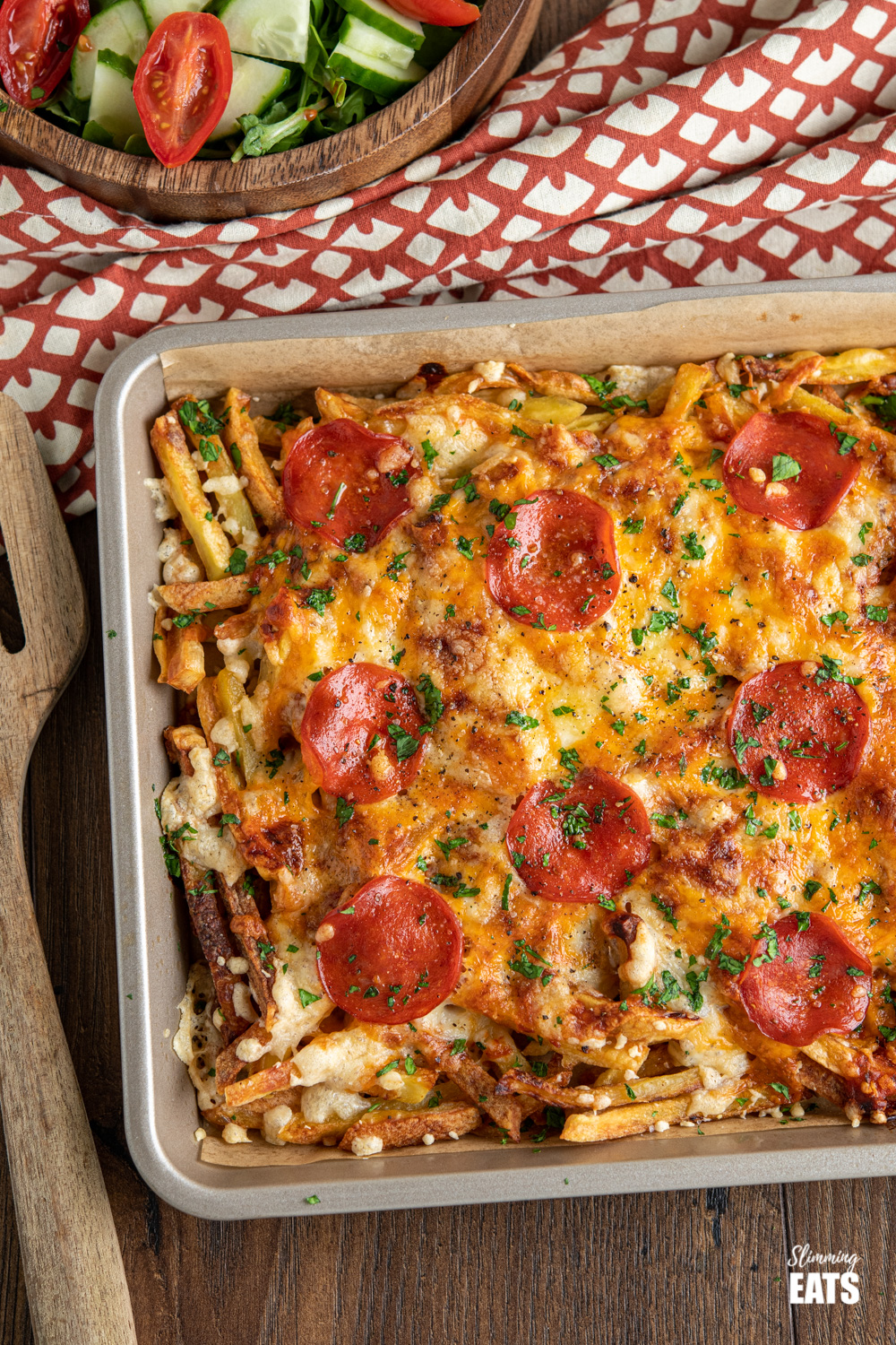 Cheesy Oven Baked Pizza Fries on baking sheet with wooden bowl filled with mixed salad