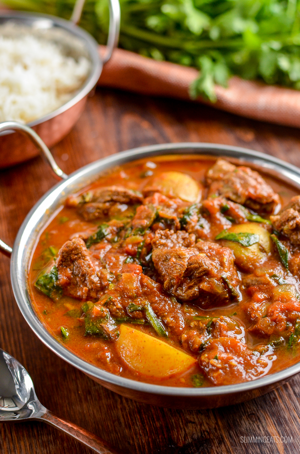 beef and potato curry in dish with rice in background