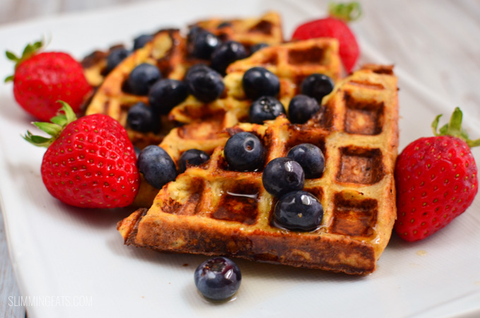 close up of French toast waffles on white plate with blueberries and strawberries