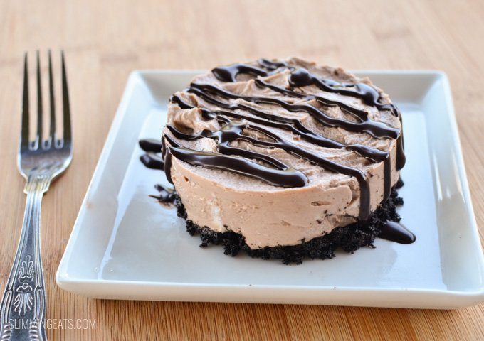 Chocolate no bake cheesecake on white plate with chocolate drizzle