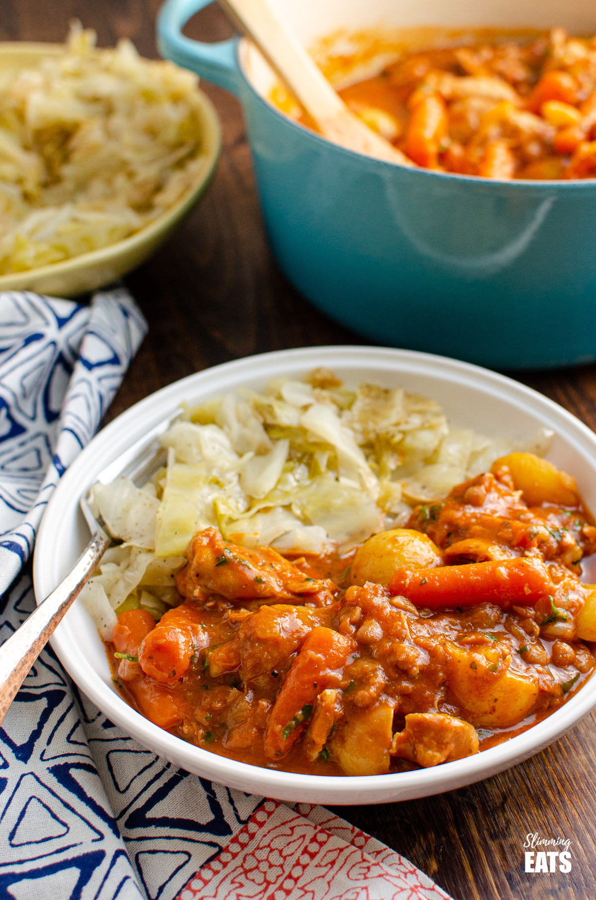 chicken and baked bean casserole in white bowl with cabbage, cast iron pot of casserole in background and bowl of cabbage