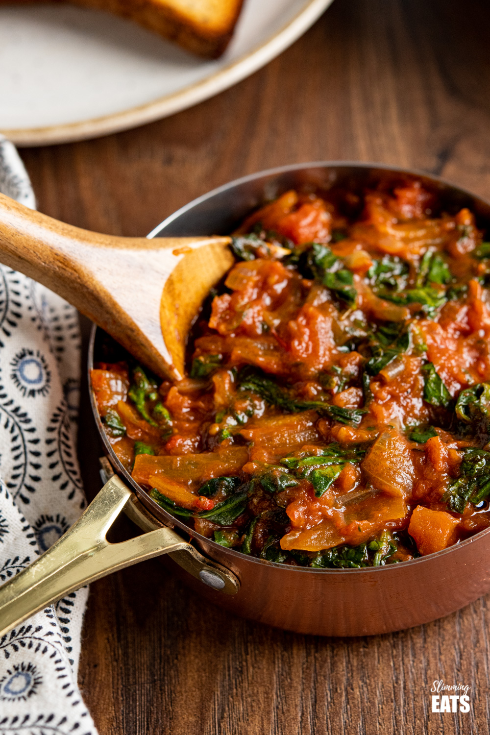 balsamic tomatoes with spinach in a copper mini saucepan with wooden spoon