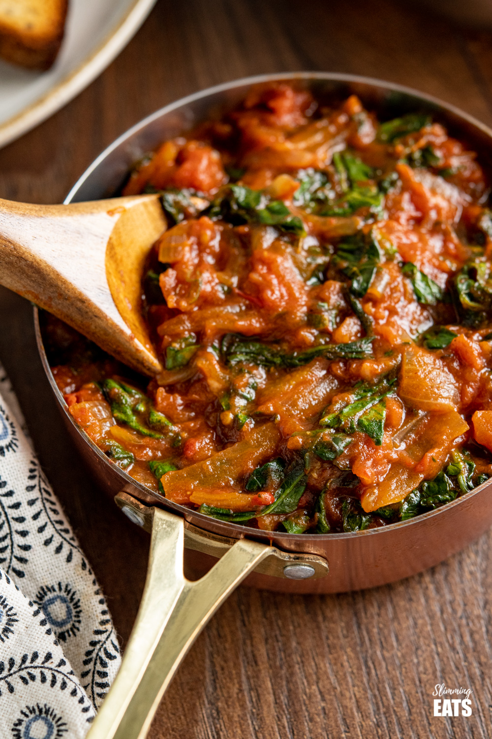 close up of balsamic tomatoes with spinach in a copper mini saucepan