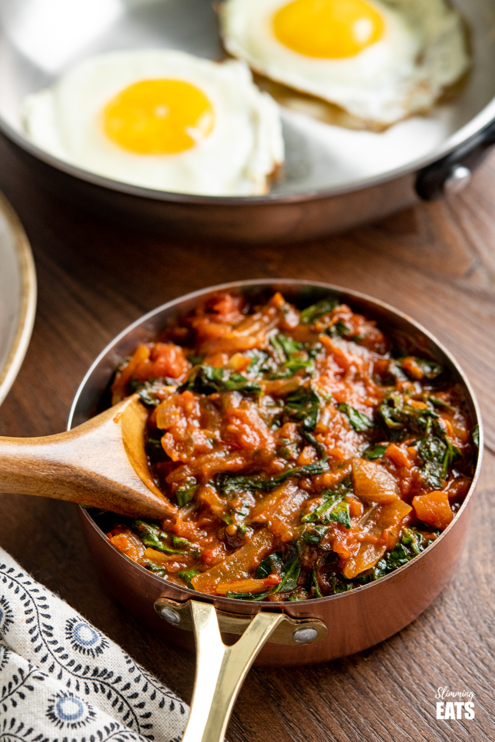 balsamic tomatoes with spinach in a copper mini saucepan with frying pan of eggs in background