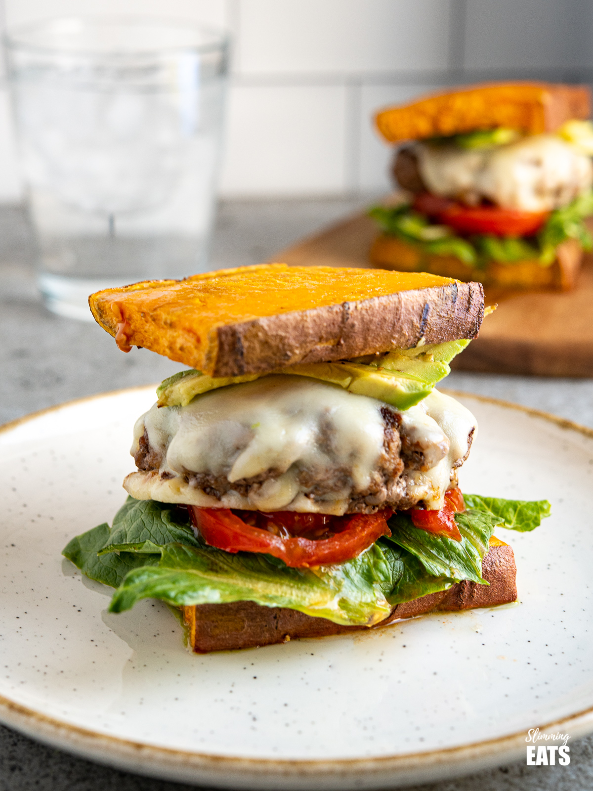 sweet potato burger sliders on a wooden board with tomato, lettuce, mozzerella, avocado and pesto on a white plate