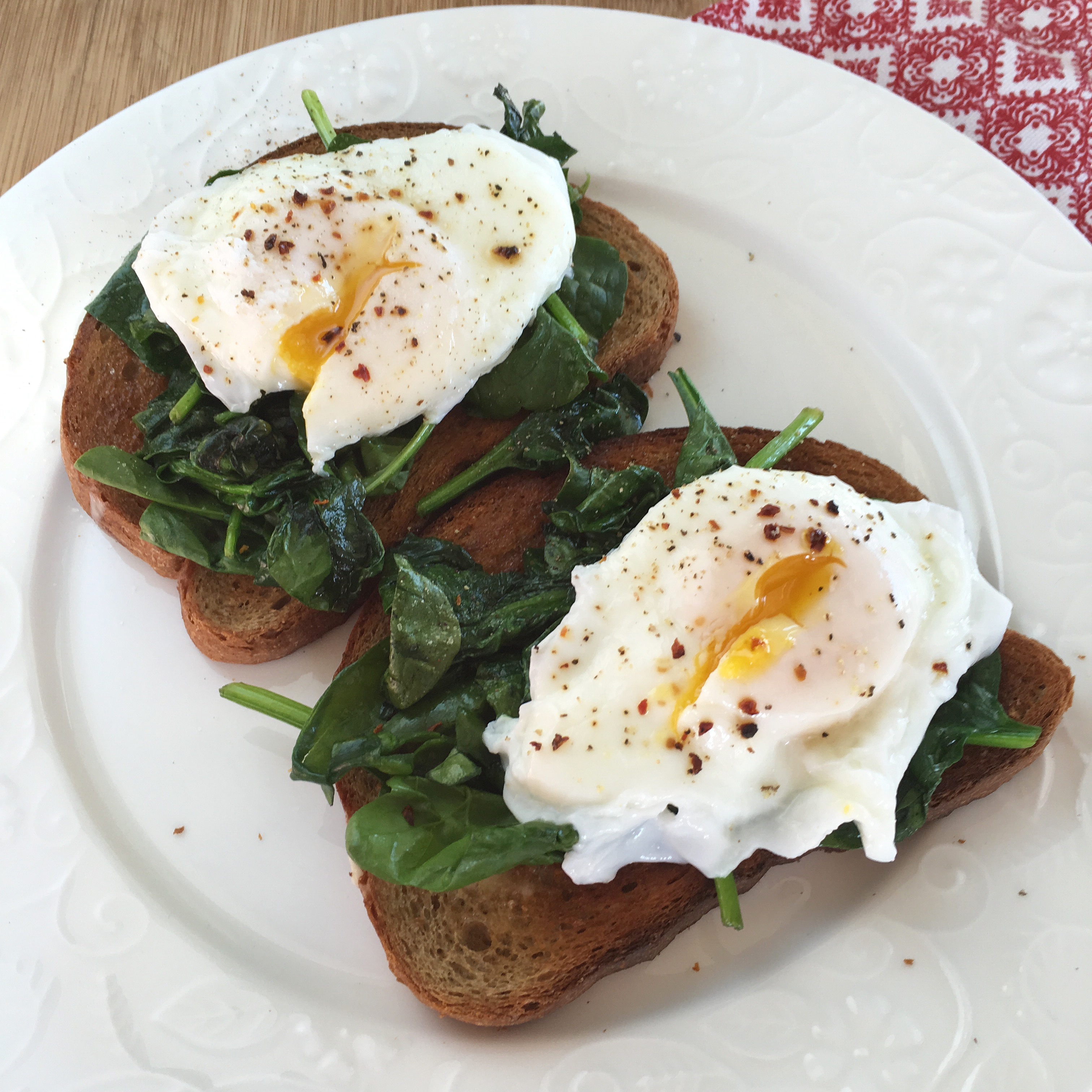 cheats poached eggs over wilted spinach and whole wheat toast on a white plate