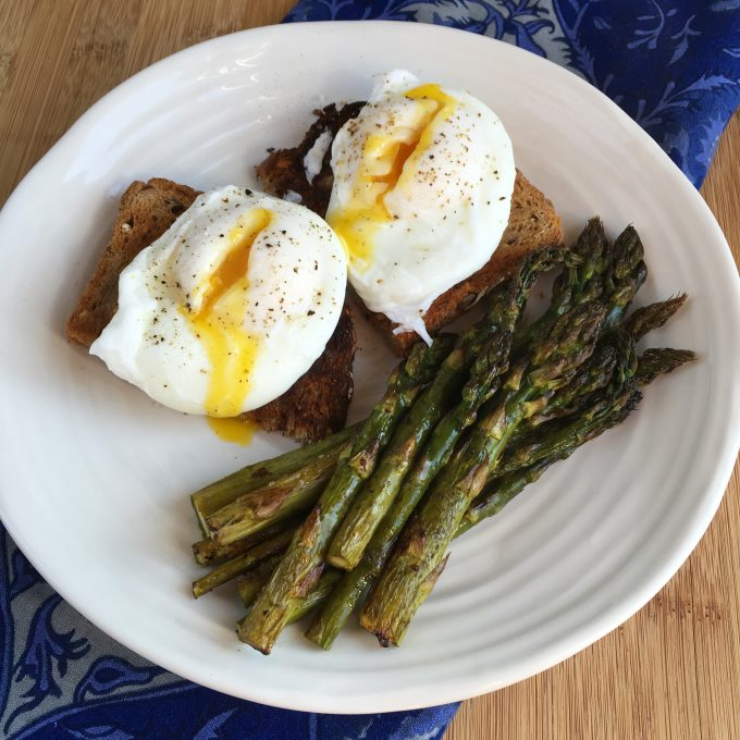 Cheats Poached Eggs on whole wheat toast with asparagus on a white plate