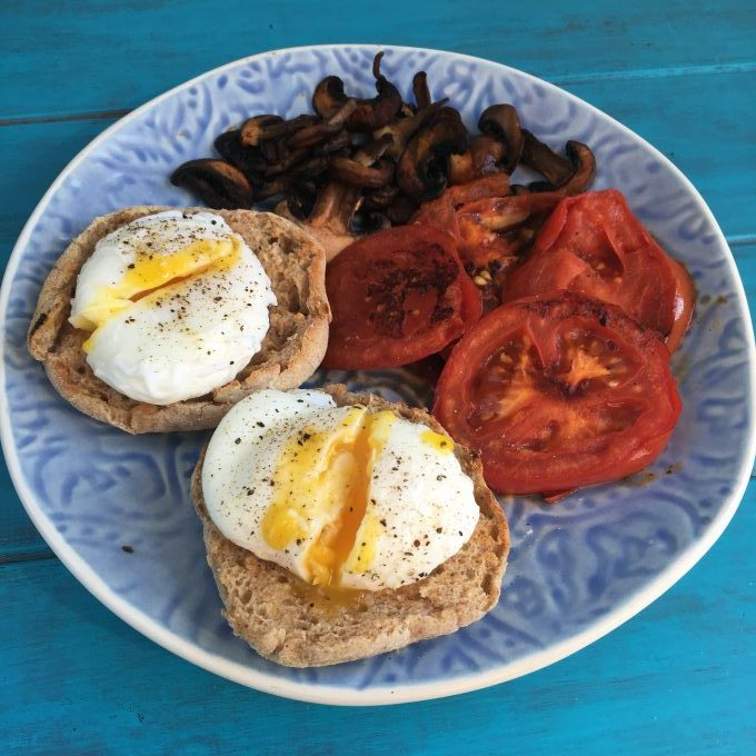 cheats poached eggs on whole wheat muffins with tomatoes and mushrooms on a blue plate