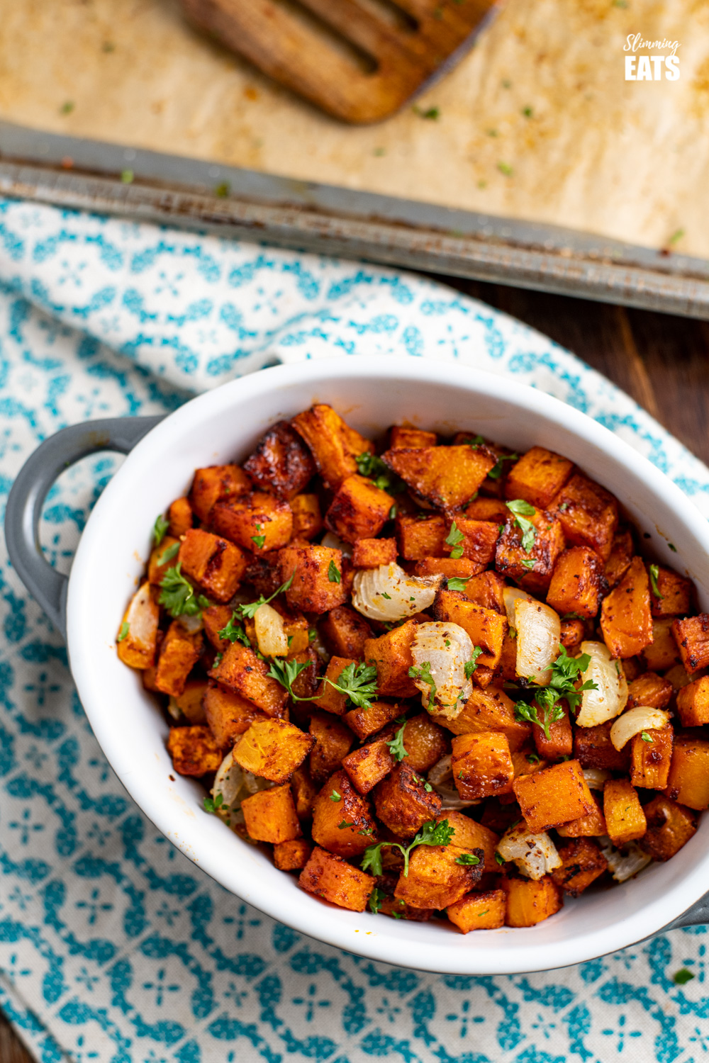roasted butternut squash in ceramic dish on patterned napkin next to baking tray