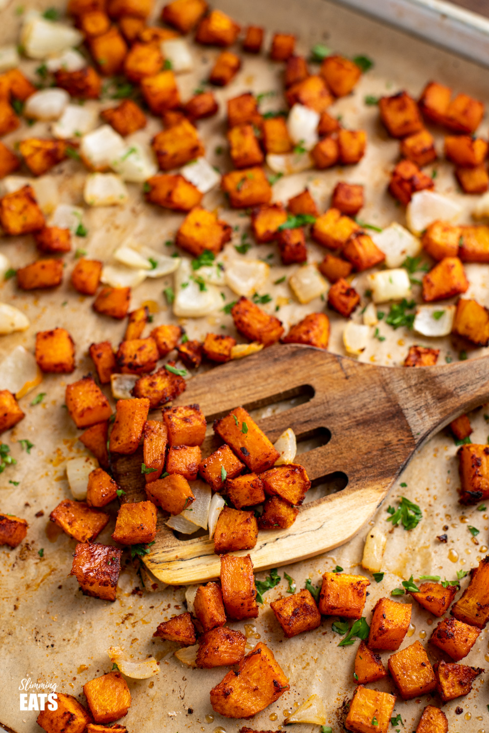 wooden spatula scooping up roasted butternut squash from parchment lined baking tray
