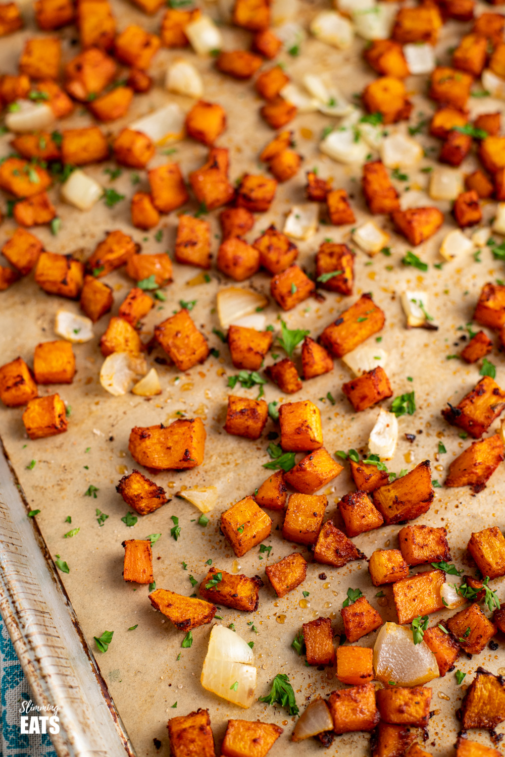 close up of seasoned roasted butternut squash on baking tray lined with parchment