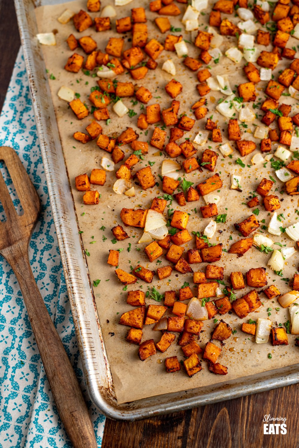 seasoned roasted butternut squash on baking tray lined with parchment paper