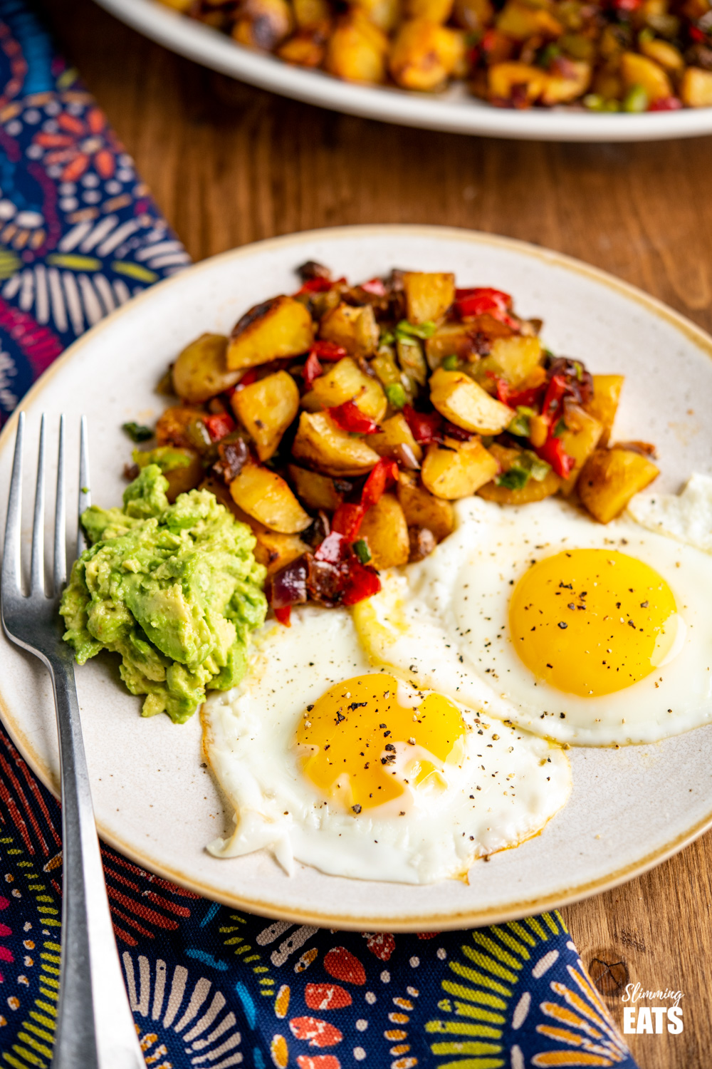 breakfast potatoes with two eggs and mashed avocado on a plate with fork.
