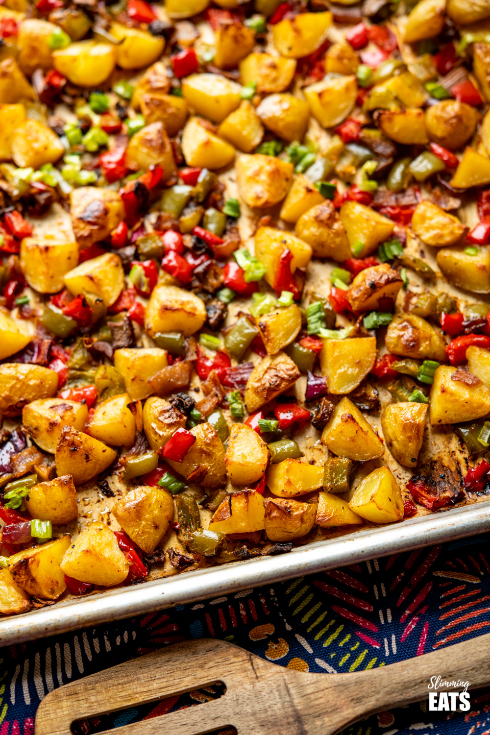 close up of breakfast potatoes on tray with wooden spatula