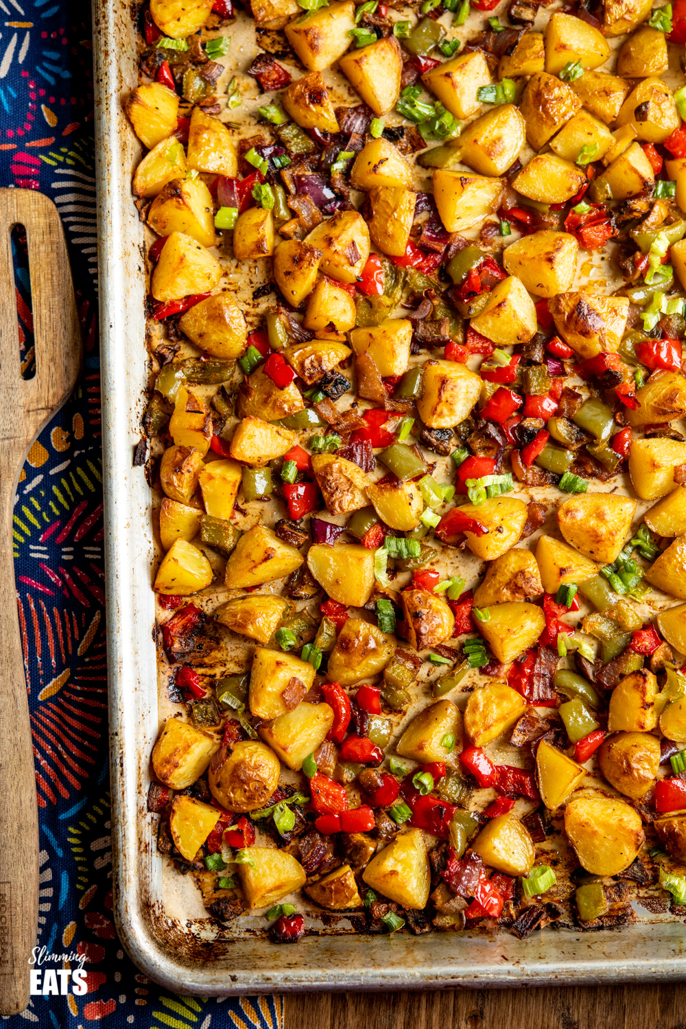 tray bake of breakfast potatoes with patterned towel on board