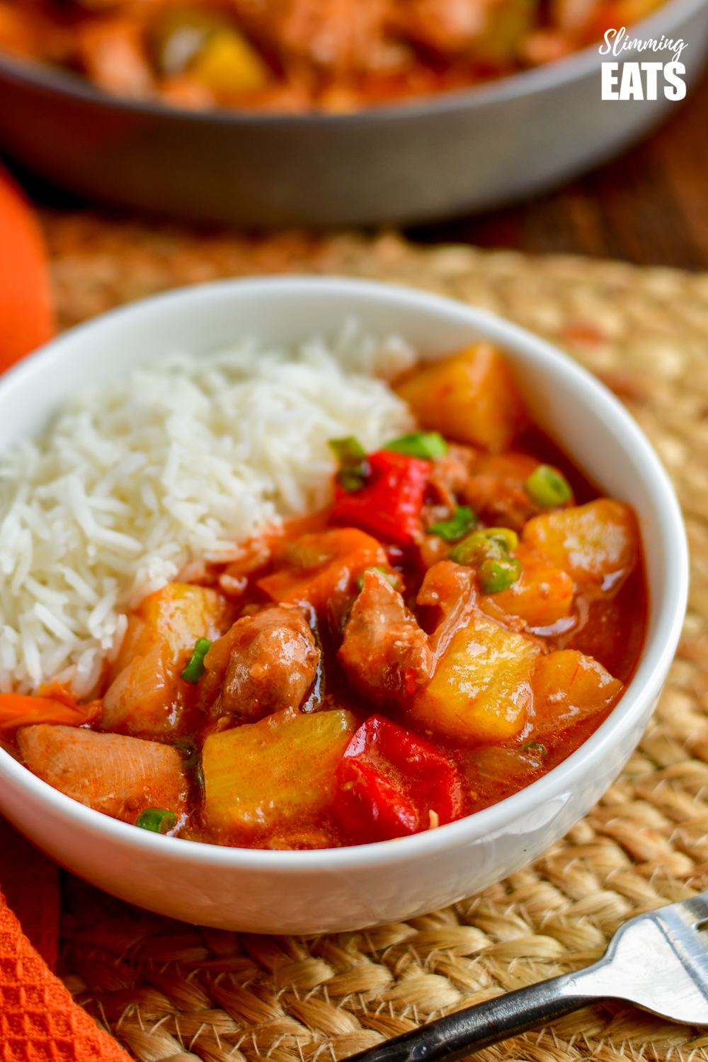 close up of instant pot sweet and sour chicken in white bowl with white rice