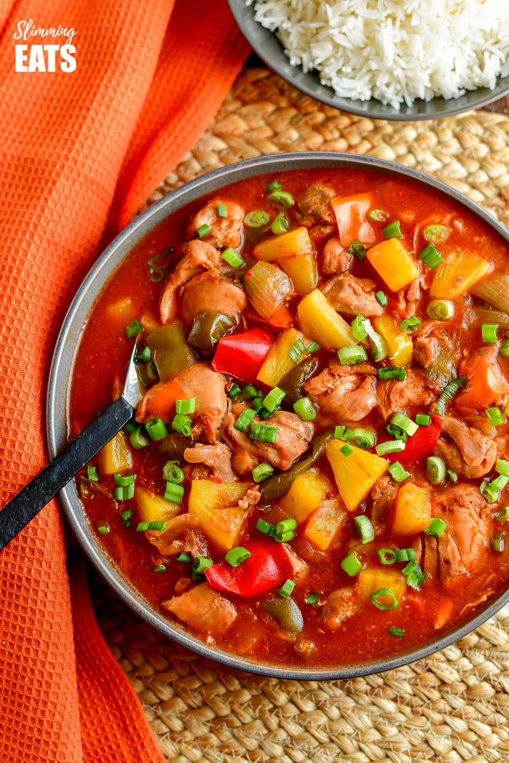 over the top view of instant pot sweet and sour chicken in grey bowl with black handled spoon.
