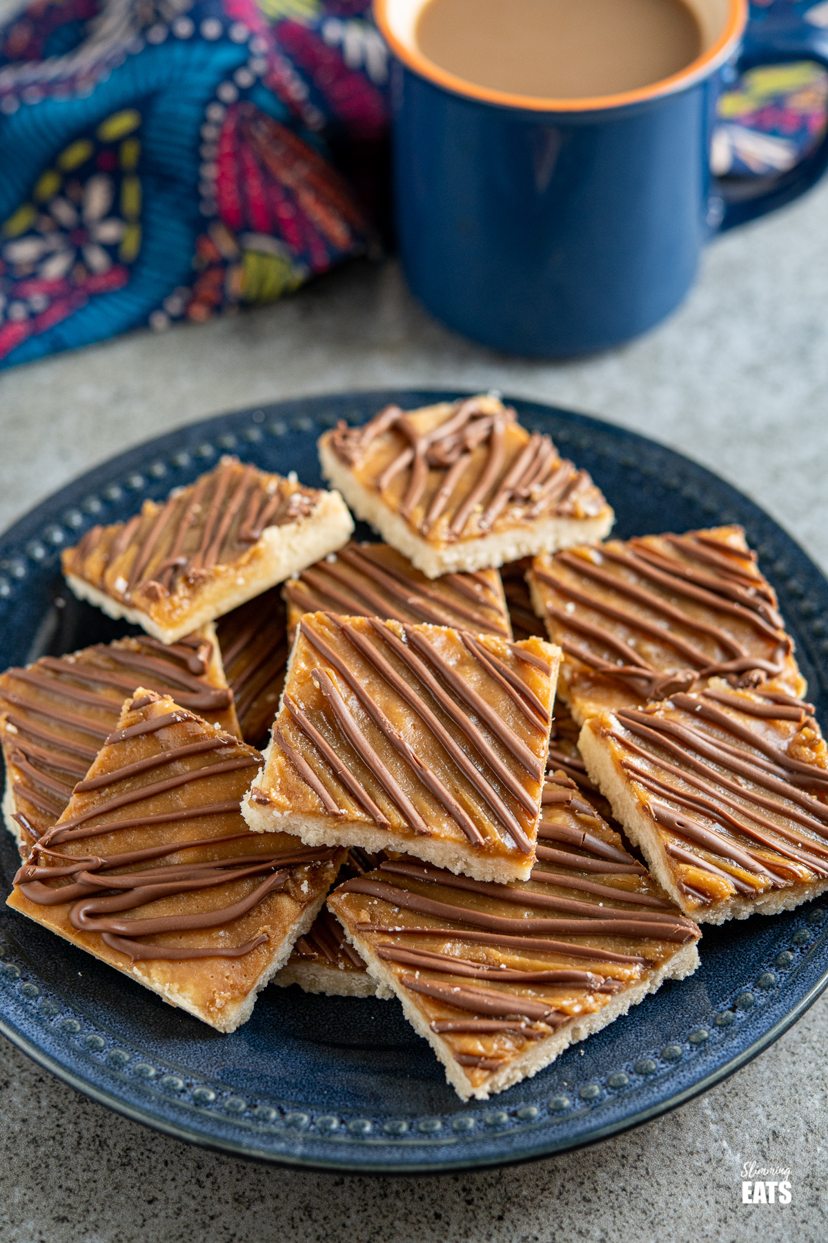 Millionaires Shortbread Squares on a dark blue navy plate with a blue mug of coffee
