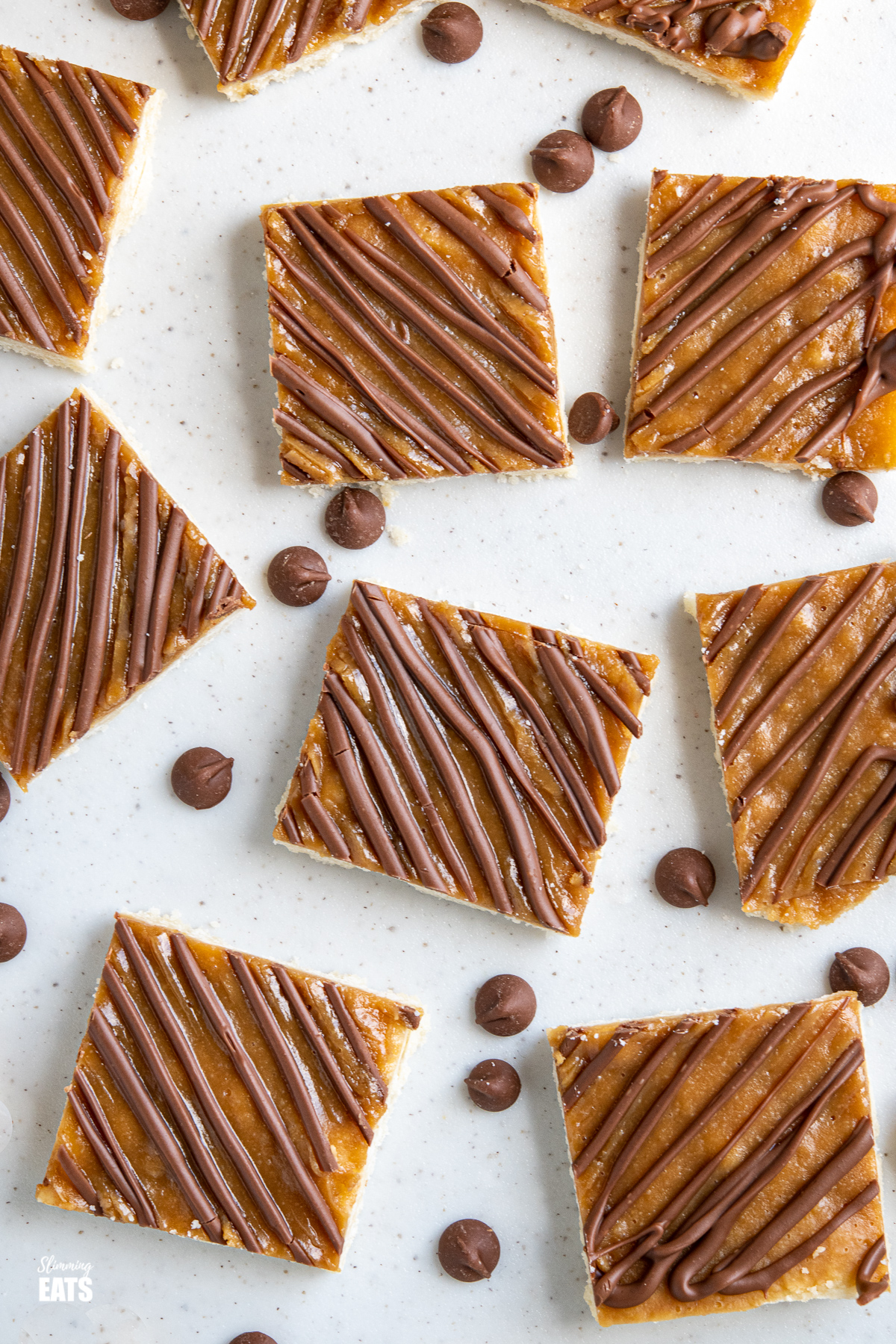 sliced  Millionaires Shortbread Squares on a white board with scattered chocolate chips