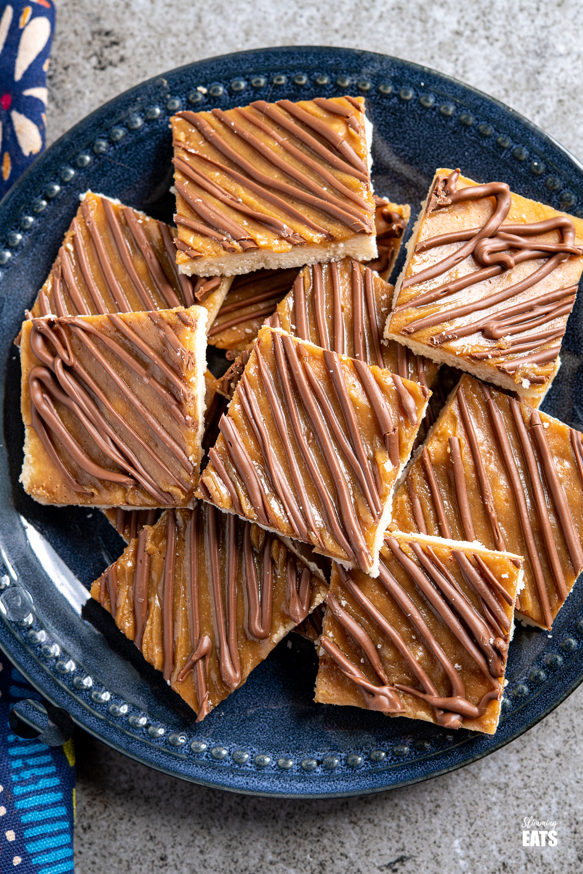 over top view of  Millionaires Shortbread Squares on a dark blue navy plate
