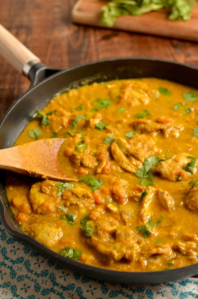 Coconut Chicken and Sweet Potato Curry in skillet with wooden spoon