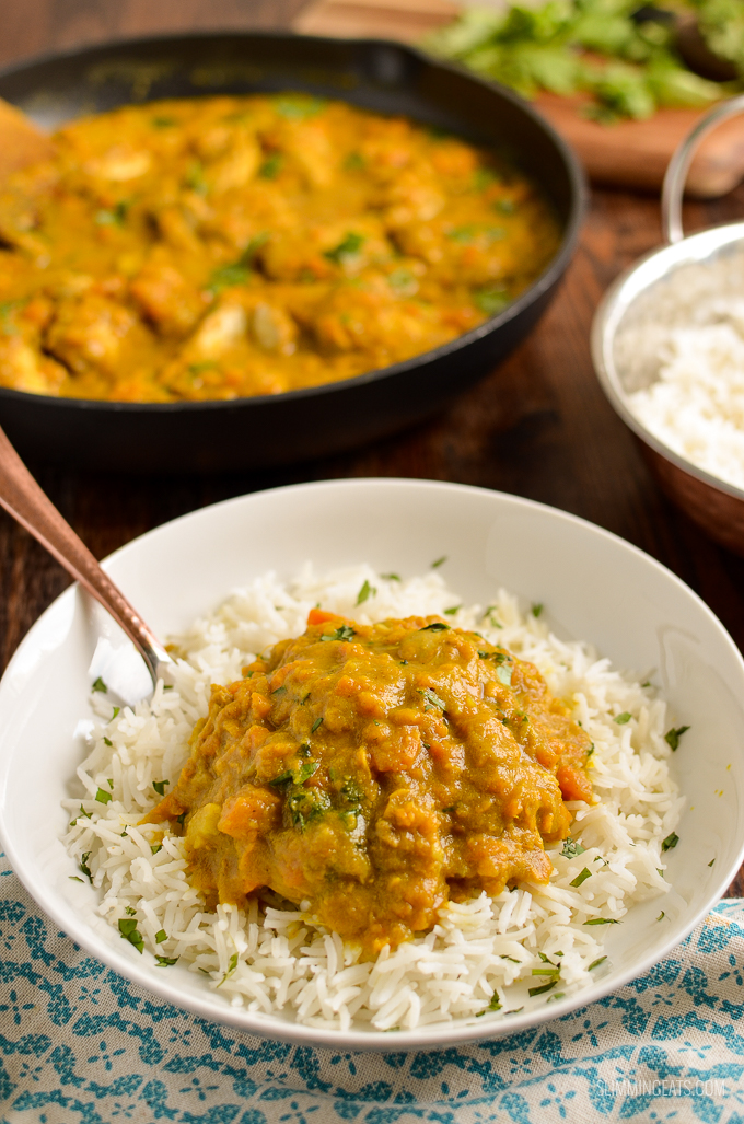 spoon in a bowl of Coconut Chicken and Sweet Potato Curry with rice