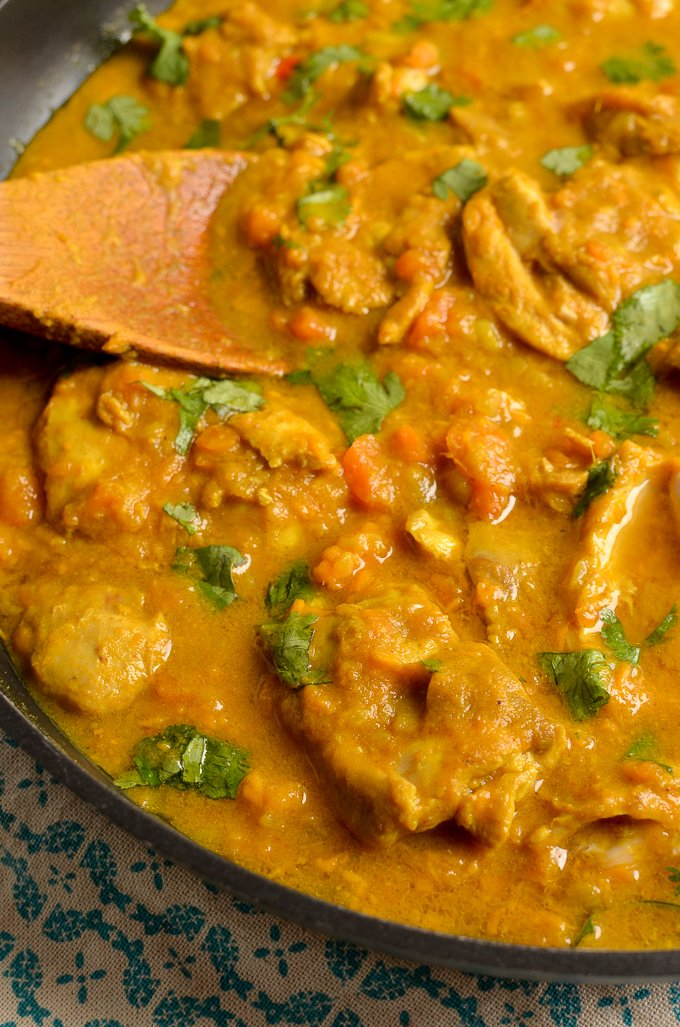 close up of Coconut Chicken and Sweet Potato Curry in skillet with wooden spoon