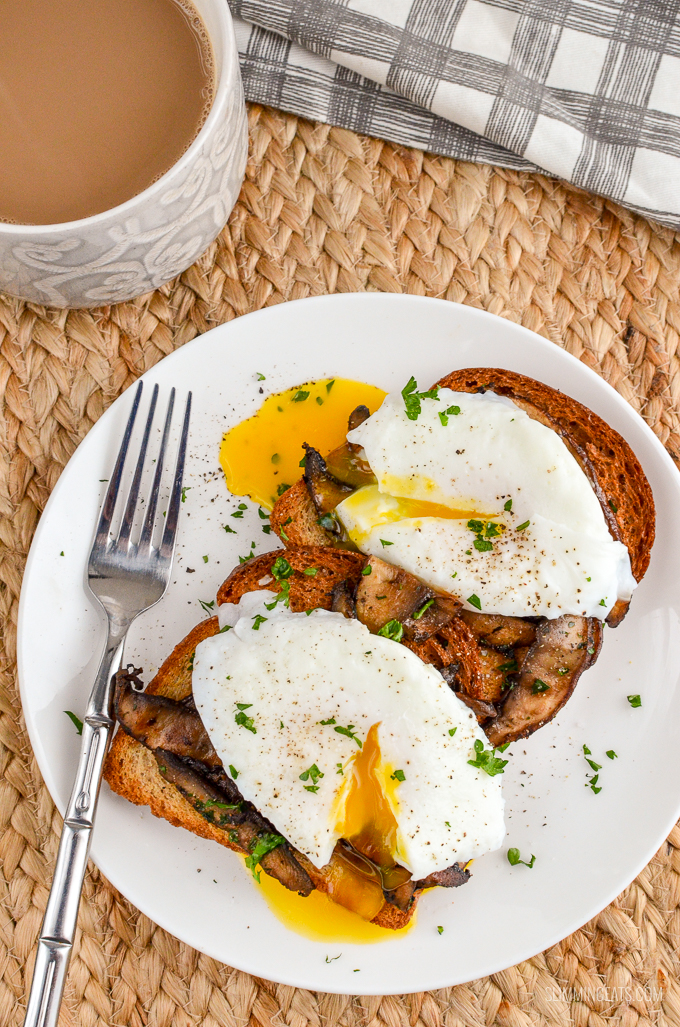 Poached Eggs over Garlic Mushrooms on whole wheat toast, over the top view, white plate and mug of coffee
