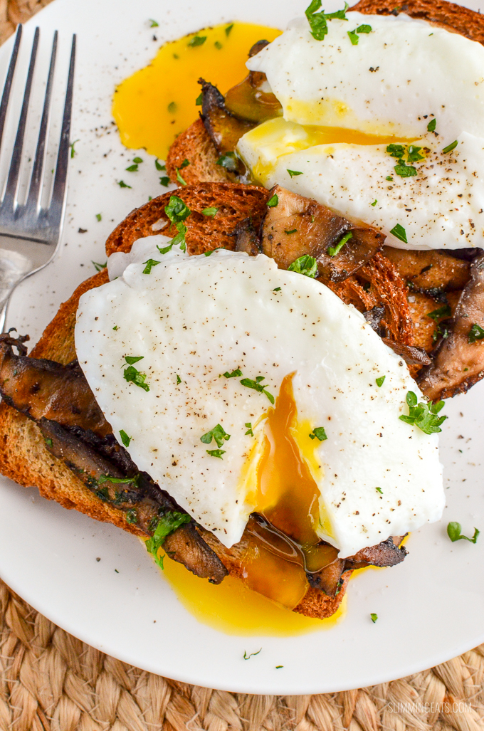 close up of poached eggs over garlic mushroom toast on a white plate with runny yolks.