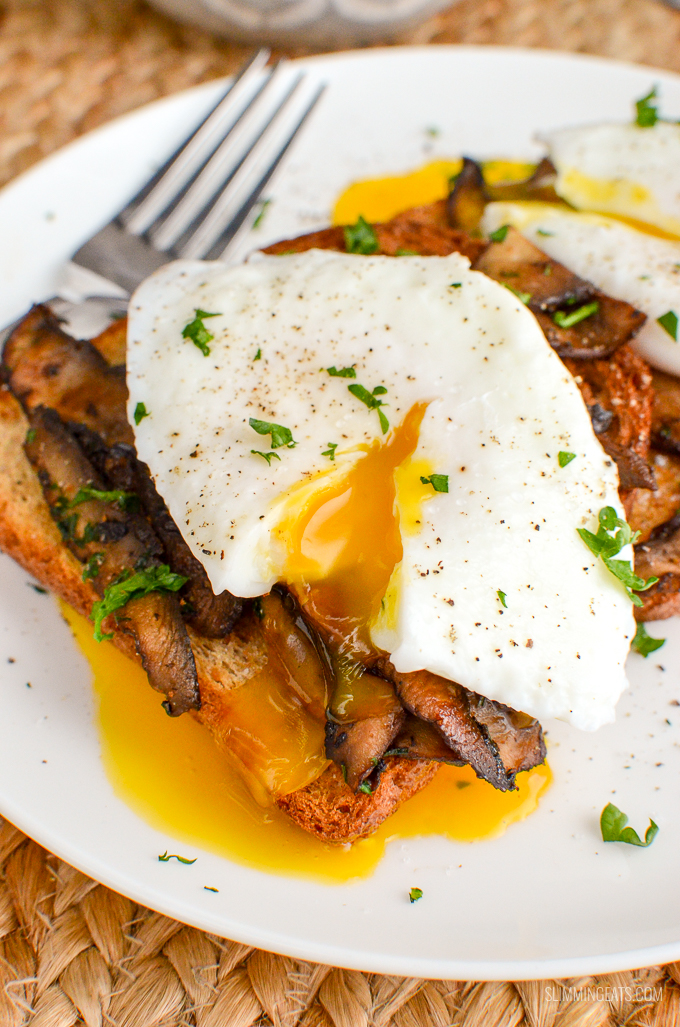 Poached Eggs over Garlic Mushrooms on toast with parsley on a white plate close up