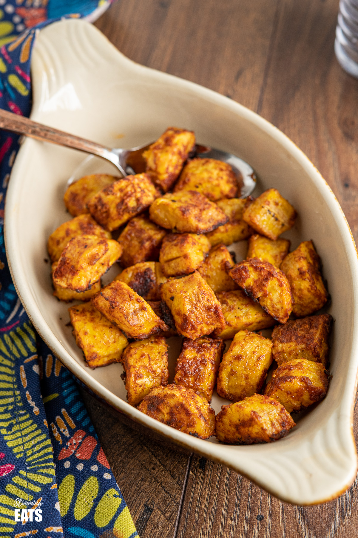 baked sweet plantain pieces in a oven oven proof brown dish with spoon on wooden board