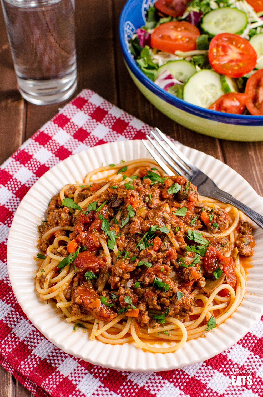 bolognese meat sauce over spaghetti on a whiter ridged plate with salad bowl and glass of water in background