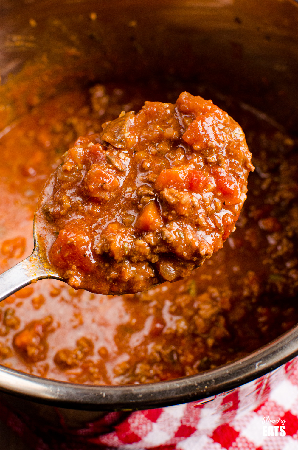 spoon scooping bolognese from instant pot pan