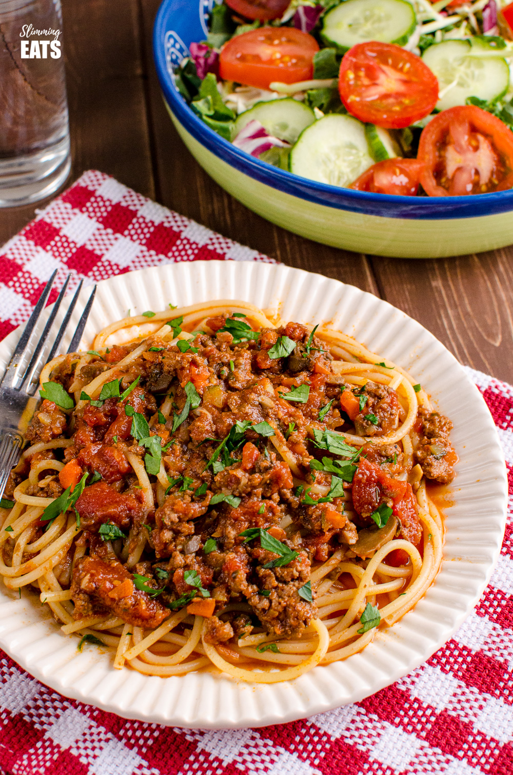 bolognese on spaghetti pasta on white ridged plate on red checked fabric with salad and water in background