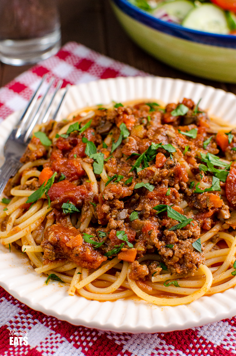 close up over bolognese meat sauce over spaghetti on red chequed placemat
