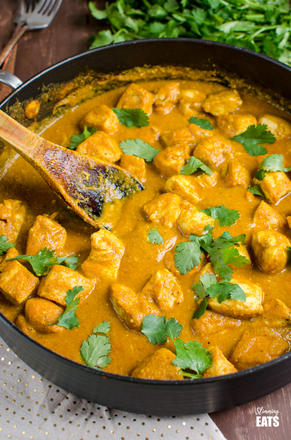 Chicken Korma in a deep black frying pan with wooden spoon and coriander in background