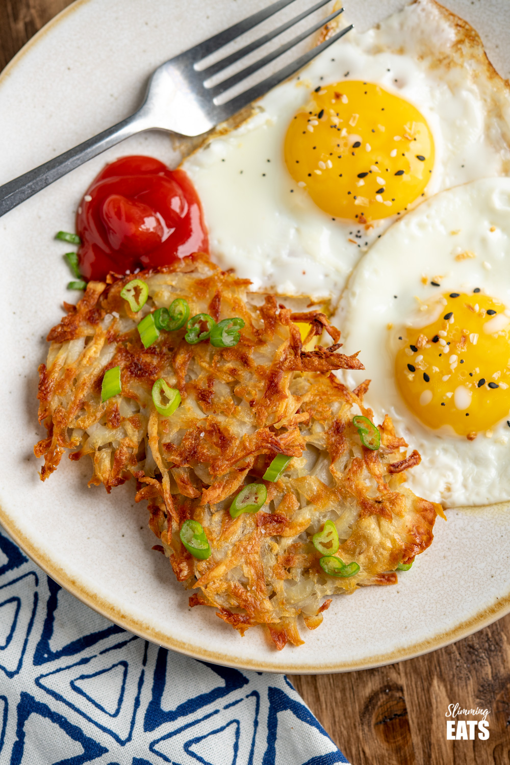 close up of Crispy Golden Hash Browns on plate sprinkled with spring onions and served with eggs and ketchup
