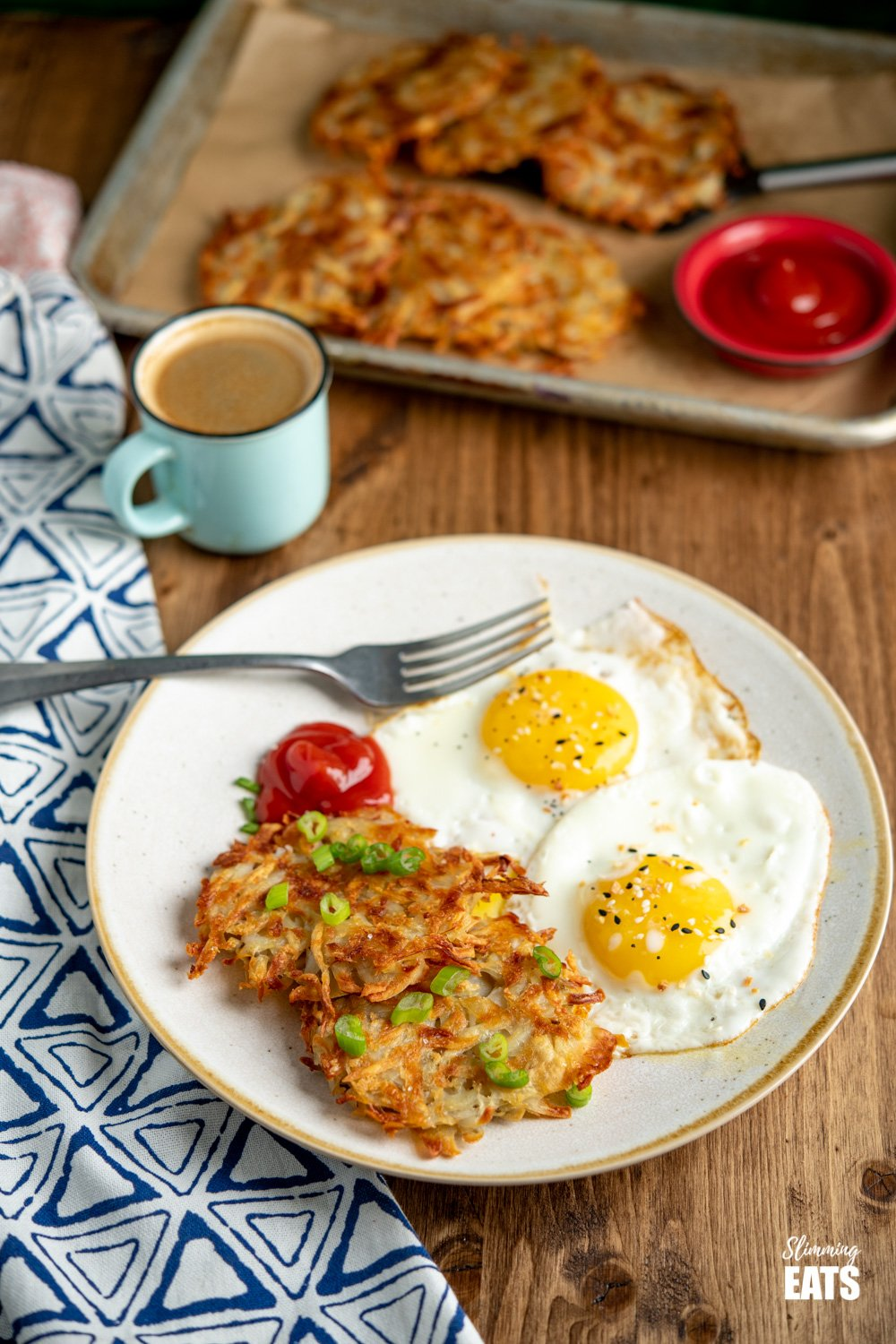 Crispy Golden Hash Browns with eggs and ketchup on a plate with silver fork, tray of hash browns in the back and mug of espresso
