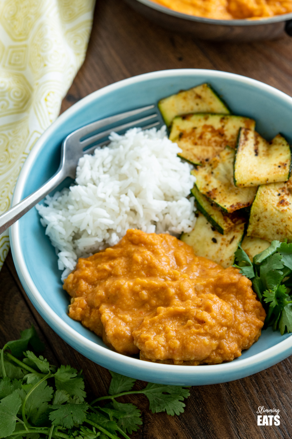 4 ingredientquick lentil curry in blue bowl with rice and sautéed zucchini and silver fork