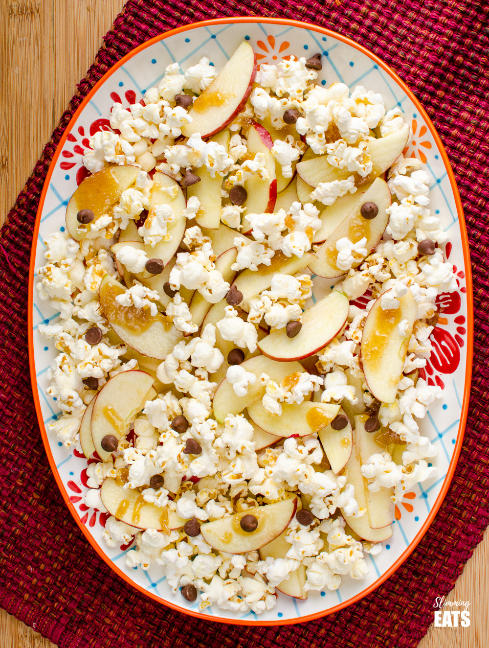 patterned oval plate filled with popcorn, chocolate chips, apple slices and caramel sauce for a sharing plate of caramel apple popcorn nachos