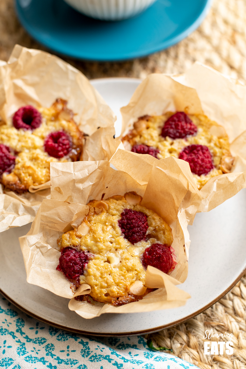 raspberry and white chocolate baked oatmeal in parchment paper on plate with cup and sauce in background