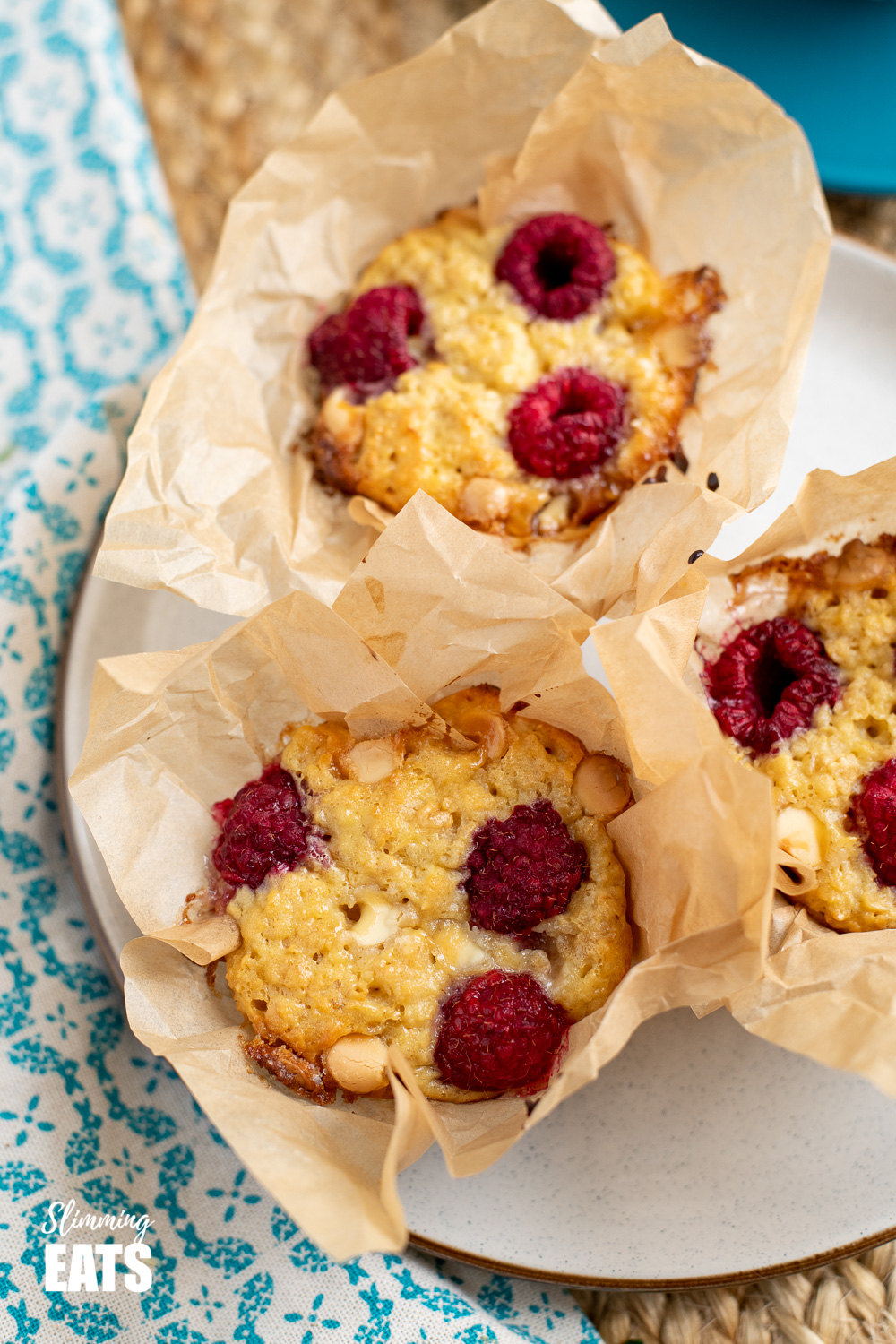 3 Raspberry and White Chocolate Baked Oatmeal in squares of parchment on plate