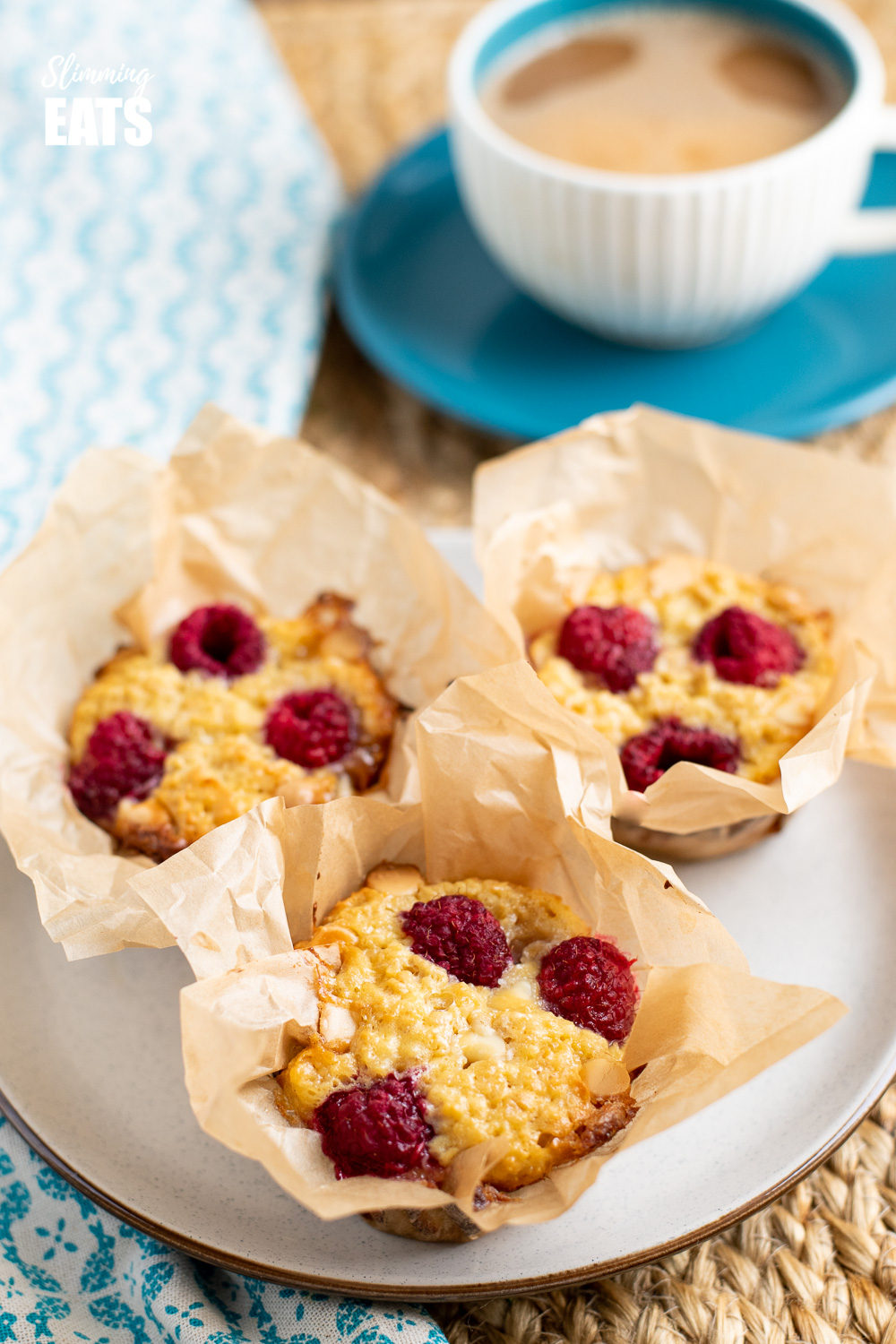 3 raspberry and white chocolate baked oatmeal in parchment paper on a plate with a cup of coffee