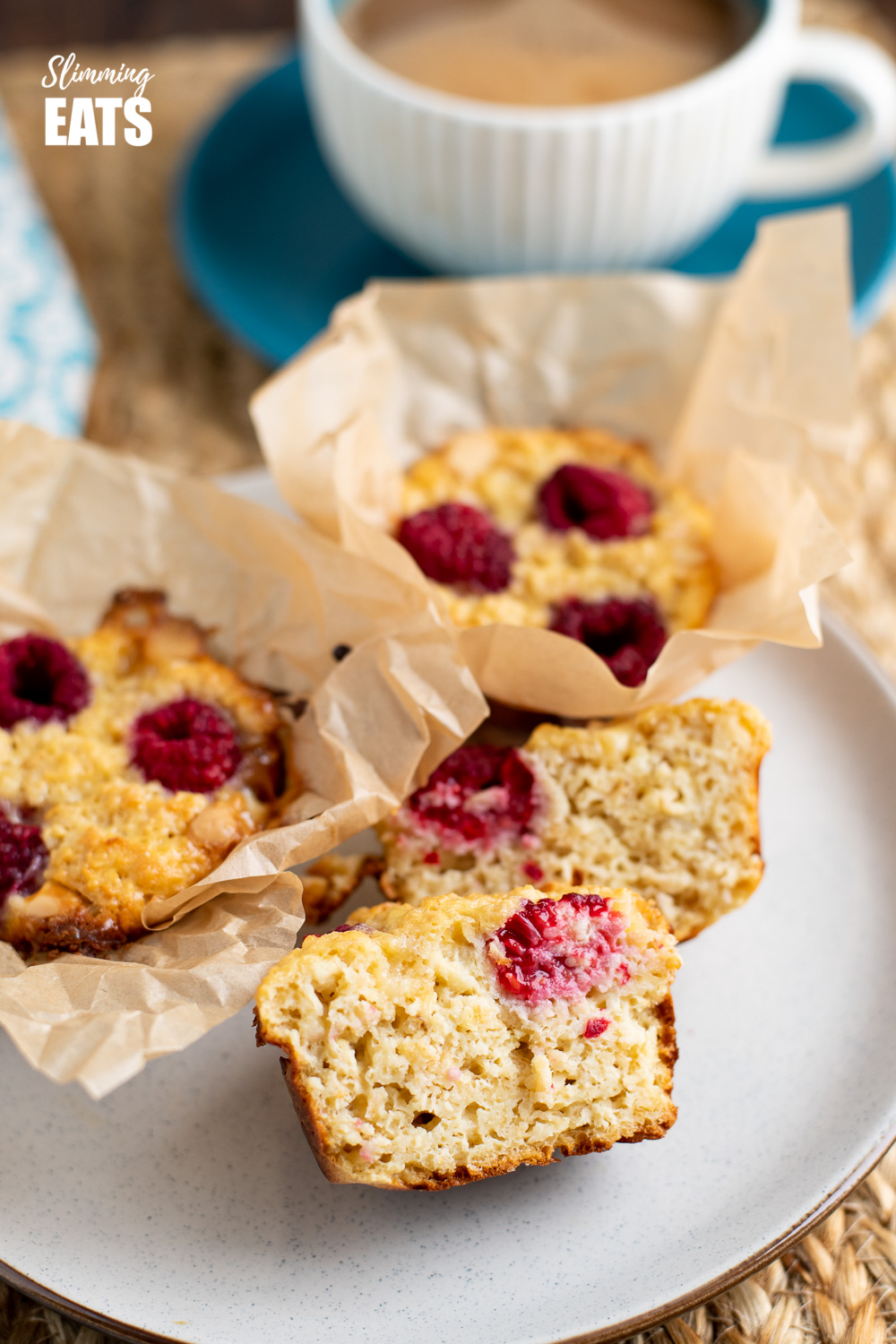 raspberry and white chocolate baked oatmeal sliced in half on plate with cup of coffee in background