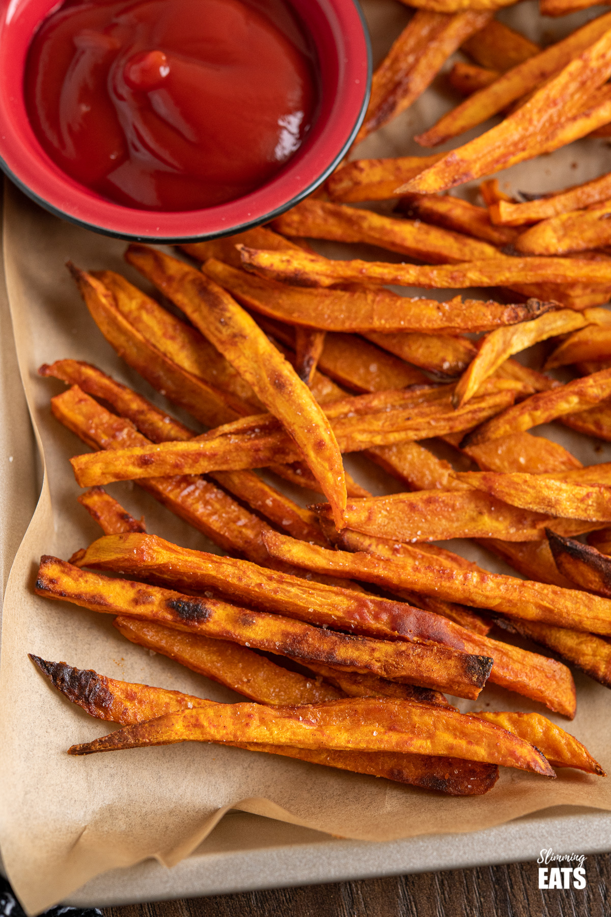 close up of Perfect Oven-Baked Sweet Potato Fries on parchment lined tray