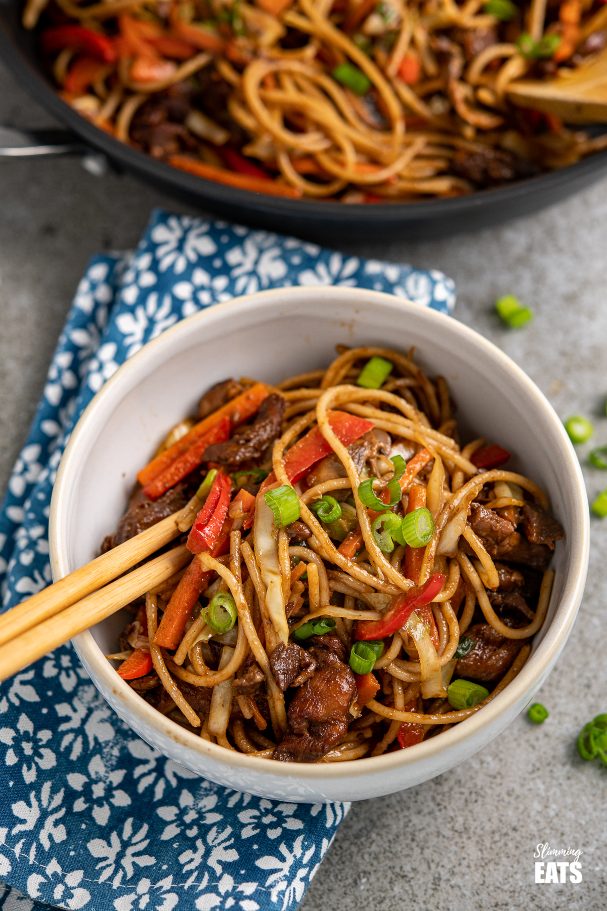 chicken with noodles and vegetables in a white bowl with chopsticks