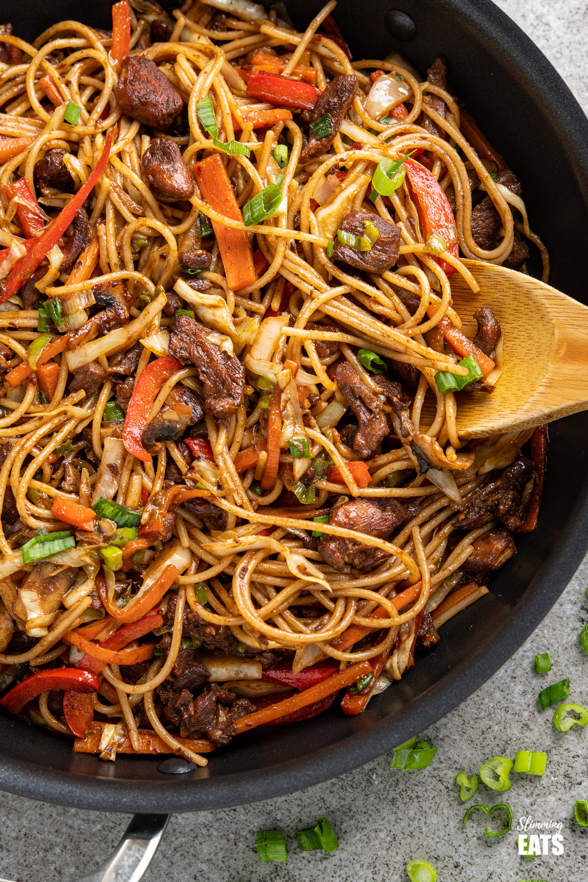 close up of chicken with noodles and vegetables in a black frying pan with scattered spring onions